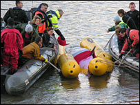 Rescuers with stranded whale on floats