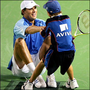 A ballboy helps Bob Bryan to his feet