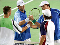 Bob Bryan and Mike Bryan (far side) shake hands with Jordan Kerr and Travis Parrott