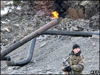 A Russian soldier guards part of the Mozdok-Tbilisi pipeline, twisted by a blast