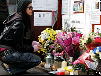 A woman looks at the floral tributes at Stockwell Tube station