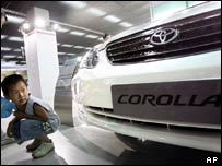 A small boy looks at a Toyota Corolla