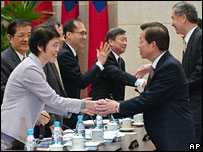 Taiwan's Premier Frank Hsieh, right, shakes hands with outgoing minister of economy before the resignation of the whole cabinet, Mon 23 Jan