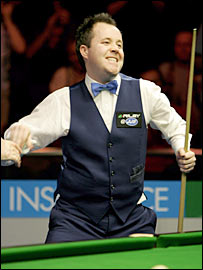 John Higgins celebrates after rolling in the final black