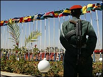 A Sudanese soldier stands guard as the flags of African countries fly in Khartoum