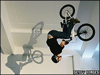 BMX stunt rider performs a forward roll while airborne