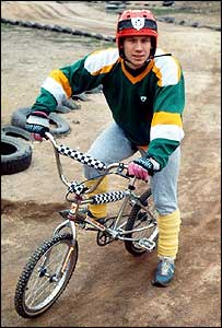 BBC presenter dressed up in BMX equipment and riding a bike