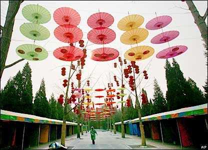 Chinese woman exercises next to paper umbrellas and red lanterns in Beijing park, 23/1/06
