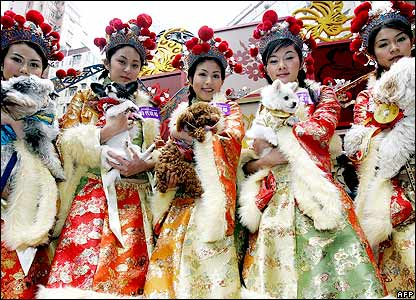Models dressed as a goddesses of wealth and holding dogs pose for photo as part of a celebration for the Chinese Lunar New Year of the Dog at a shopping mall in Hong Kong, 23 January 2006. T