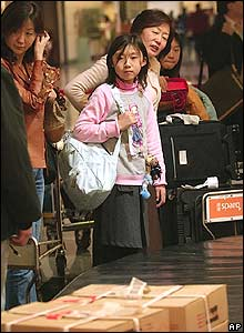 People wait for their luggage after arriving from Shanghai to the Chiang Kai-shek airport in Taoyuan, Taiwan, 40km (24 miles) southwest of Taipei, Friday, Jan. 20, 2006.
