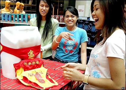 Shopper shares a light moment while looking at reversible bright red briefs with Chinese characters in gold on display and for sale at a shopping centre in Johor, southern Malaysia, Jan. 19, 2006.