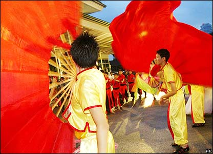Street performers are seen carrying giant fans during a street performance rehearsal, Saturday Jan. 21, 2006 in Singapore