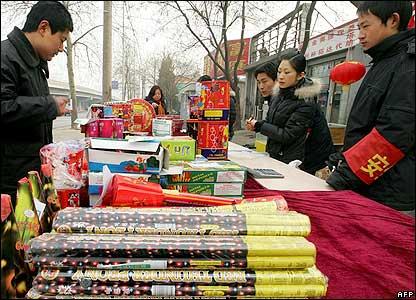 A customer looks for fireworks as vendors prepare their display for sale to the public, 23 January 2006 in Beijing.