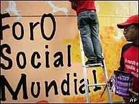 Hombres pintan una pared con el lema del Foro Social Mundial