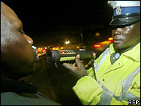 A Kenyan police officer tests the alcohol intake of a driver in Nairobi.
