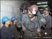 Miners bring out a colleague hurt in a blast at Dongfeng mine, Heilongjiang province, in November 2004.