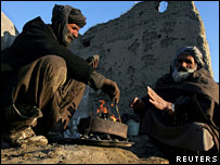 Afghan men in front of teashop in ruins