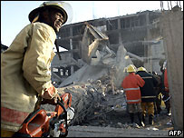 Rescue workers in front of the collapsed building