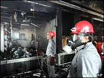 Iranian firemen inspect the damage inside the bank in Ahwaz