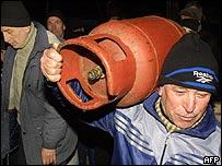 Habitante de Georgia cargando un cilindro de gas.