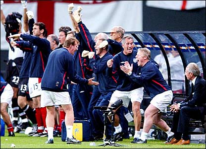 Sven-Goran Eriksson sits (right) while the England bench celebrate David Beckham's penalty winner against Argentina
