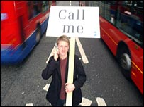 Man with sign reading 'Call me'