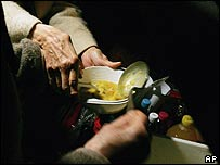 Volunteers pour pork soup into a bowl during a free distribution to the homeless in Paris