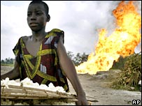 Nigerian resident standing in front of oil blaze
