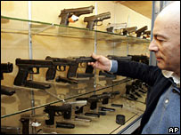 A man looks at guns in a gun shop in Naples, Italy