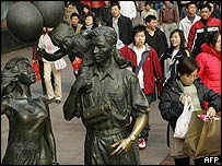 Shoppers pass a statue in Shanghai