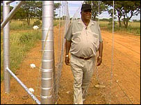 Payete Ndlovana, walking beside an electric fence