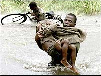 A Mozambican soldier tries to save a child in the floods of  2000
