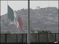 Bandera mexicana tras muro fronterizo.