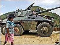 An indigenous woman in front of a Colombian tank