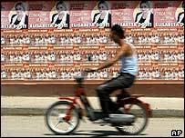Motorcyclist passes election posters in Tirana