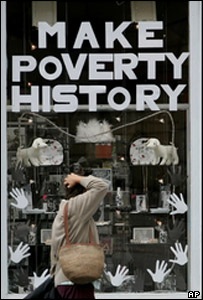 Woman standing in front of a Make Poverty History sign in Edinburgh