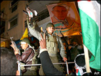 Fatah supporters wave guns and flags as they celebrate in Gaza City