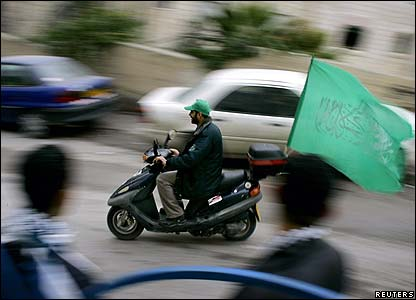 Hamas supporter on moped drives past Fatah supporters outside polling station