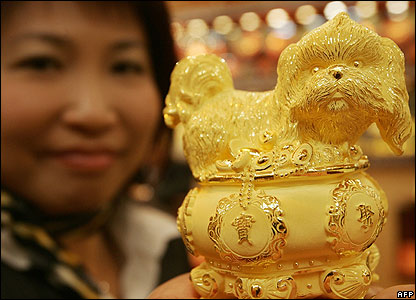 A shop assistant in Hong Kong holds a solid gold dog