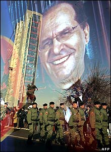 Soldiers carrying the coffin reflected in a portrait of Ibrahim Rugova