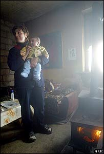 Tbilisi mother and child keep warm beside a stove in their home