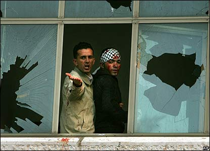 Fatah supporters at broken window in Ramallah