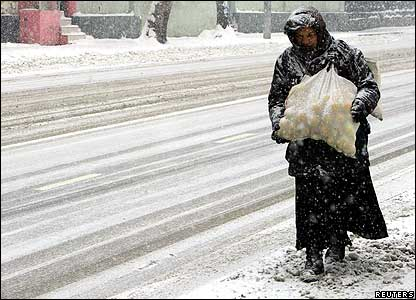 Woman carries a sack of apples through snow in Tbilisi