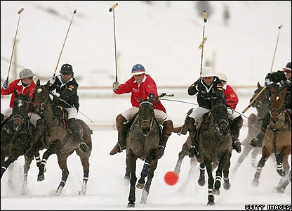 Polo players battle for the ball during a match on a frozen lake