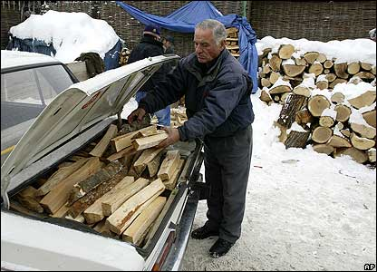 Man loads his car with firewood he bought at a market in Tbilisi