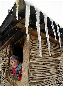 Woman looks out from booth covered in icicles at a market in Tbilisi