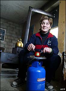 Woman uses gas canister in her home in Tbilisi