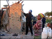 A Zimbabwean man stands by as police destroy his home