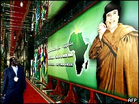 A delegate in a hallway of the Sirte conference centre observes a billboard with Libyan president Muammar Gaddafi .
