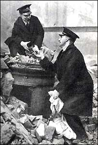Postmen empty a pillar box buried in rubble in Second World War
